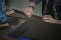 Leather manufacturer working with tool on wooden table with leather Stock Photography