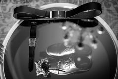 Ring, leather men`s shoes with belt and bow tie. Set of groom accessories on wedding day. Black and white photo stock photography