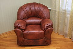 A leather modern arm-chair. Is in a new cottage Royalty Free Stock Images