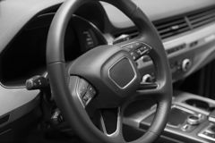 Leather multifunction steering wheel in the cabin of a premium car. Installed under the steering wheel control switches additional. Functions. Behind the wheel royalty free stock photos