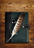 Leather notebook and feather with ink bottle. Royalty Free Stock Image
