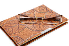 Leather  notebook and glasses isolated. On a white background Royalty Free Stock Photos