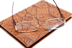 Leather  notebook and glasses isolated. On a white background Royalty Free Stock Image