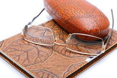 Leather  notebook and glasses isolated. On a white background Stock Image