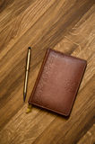 Leather notebook and golden pen. Royalty Free Stock Image