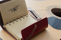 Leather notebook with pen picture of an airplane on the background of a guitar Royalty Free Stock Image