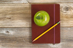 Leather notepad with apple and pencil for school or office on ru. Top view of green apple, leather notepad and pencil on rustic wood Royalty Free Stock Photography