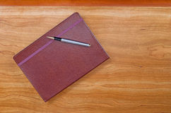 Leather notepad with pen on cherry wood desktop Royalty Free Stock Photos