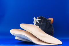Leather orthopedic insoles with boot. Blue background. Royalty Free Stock Images