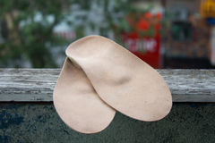 Leather orthopedic insoles on an old wooden board outdoors. Royalty Free Stock Photo