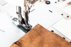 Leather piece and presser foot of sewing machine. Leather piece and presser foot of industrial sewing machine close up royalty free stock photography