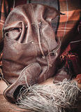 Leather products against the background of wool tartan. Leather backpack and shoes on the background of wool tartan on the wooden floor Stock Photos