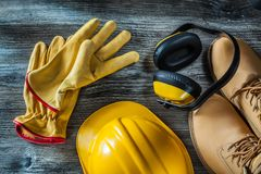 Leather protective gloves boots hard hat earmuffs on wooden boar. D royalty free stock photos