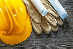 Leather protective gloves construction plans hard hat on wooden Royalty Free Stock Images
