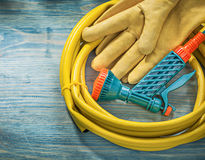 Leather protective gloves garden hose on wooden board gardening. Concept stock photo