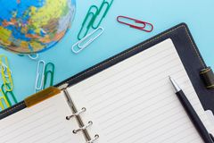 Free Leather Ring Planner With Black Pen, Globe And Colorful Clips Open On Blue Workspace Stock Images - 154605654