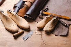Leather in rolls, cobbler tools and shoe lasts in workshop. Leather craft tools. royalty free stock photography