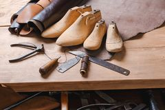 Leather in rolls, cobbler tools and shoe lasts in workshop. Leather craft tools. royalty free stock photo