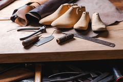 Leather in rolls, cobbler tools and shoe lasts in workshop. Leather craft tools. stock photo