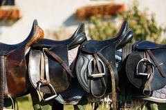 Leather saddle horse. A saddles laying on the rustic fence in warm sunlight Royalty Free Stock Photos