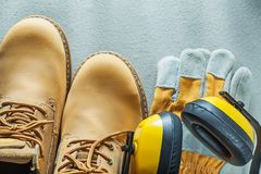 Leather safety boots gloves earmuffs on concrete background Royalty Free Stock Images