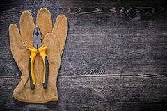 Leather safety glove tin snips on wooden board Stock Images