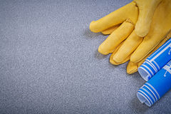Leather safety gloves blue rolled construction plans on grey bac Royalty Free Stock Images