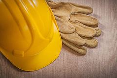 Leather safety gloves building helmet on wooden board constructi Stock Photography