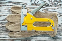 Leather safety gloves construction stapler on wooden board.  royalty free stock image