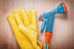 Leather safety gloves garden hose nozzle on wooden board gardeni. Ng concept royalty free stock images