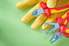 Leather safety gloves insulation strippers nippers pliers on gre Stock Image