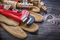 Leather safety gloves monkey wrench brass plumbing connectors ba Stock Images