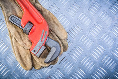 Leather safety gloves pipe wrench on channeled metal plate const Stock Photography