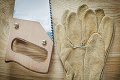 Leather safety gloves sharp hacksaw on wooden board construction Stock Photography