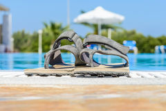 Leather sandals are on the edge of the swimming pool Royalty Free Stock Photography