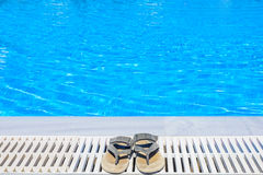 Leather sandals are on the edge of the swimming pool Royalty Free Stock Photos
