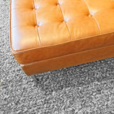 Leather seat on gray wool carpet. Close-up of a leather seat on gray wool carpet. Modern design stock photo