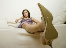 Leather shoes. Young woman is sitting on sofa in leather shoes Royalty Free Stock Image
