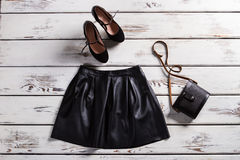 Leather skirt and suede shoes. Skirt and footwear on shelf. Fashionable clothes for modrn girls. Lady's trendy evening clothes Royalty Free Stock Image