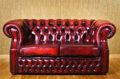 Leather Sofa. Red Genuine Leather Sofa Near The Wall Stock Photo