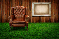 Leather sofa on green grass and photo frame Royalty Free Stock Photography