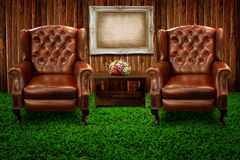 Leather sofa on green grass and photo frame Stock Photos