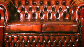 Leather Sofa. Red Genuine Leather Sofa Near The Wall Royalty Free Stock Photos