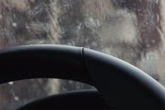 Leather steering wheel, rain windshield bokeh Royalty Free Stock Photos