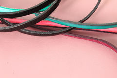 Leather strips laces motif in vivid colors on pink pastel leather background Stock Photo