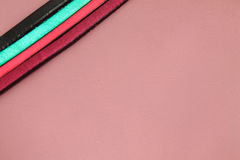 Leather strips laces motif in vivid colors on pink pastel leather background Stock Photos