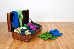 Leather suitcase full of colorful clothing. Leather suitcase on a wooden floor in an empty room, full of colorful clothing royalty free stock image