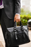 Leather suitcase in hand. Person in suit holding men bag. Leather suitcase in man`s hand. Person in suit holding elegant men`s bag. Fashion accessory for males stock photo