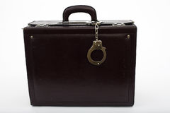 Leather suitcase from pinned handcuffs Royalty Free Stock Images