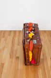 Leather suitcase with too much clothing. Leather suitcase on a wooden floor, overfilled with clothing stock images